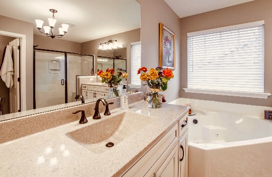 A kitchen with a sink mirror and window Description automatically generated
